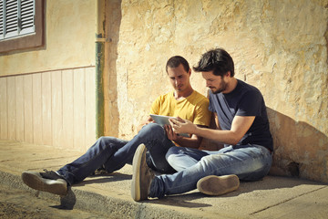Young men watching something on a tablet