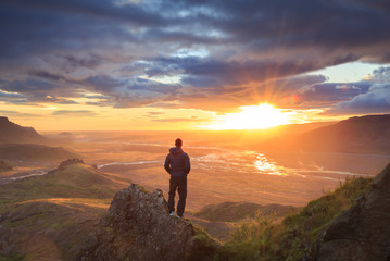 Hiker standing on a ledge of a mountain, enjoying the beautiful sunset over a wide river valley in Thorsmork, Iceland.