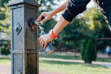Runner with red clock takes water on a break