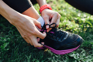 Closeup of a sportswoman tying shoelaces
