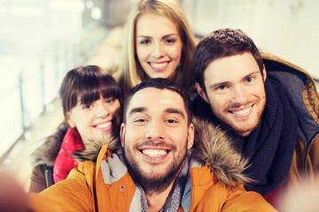 happy friends taking selfie on skating rink