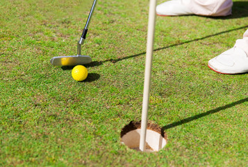 close up of man with club and ball playing golf