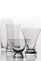 four decorative glasses on a mirrored desk