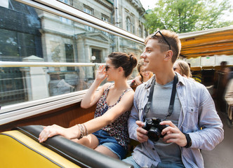 Fototapeta smiling couple with camera traveling by tour bus obraz