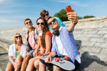 happy friends with smartphone taking selfie