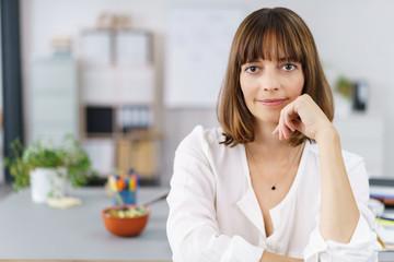 entspannte geschäftsfrau in ihrem büro schaut in die kamera