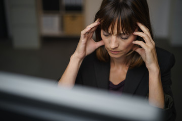geschäftsfrau arbeitet abends am pc und hat kopfschmerzen