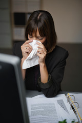 frau im büro ist erkältet und putzt sich die nase