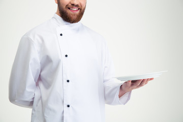 Happy male chef cook holding empty plate