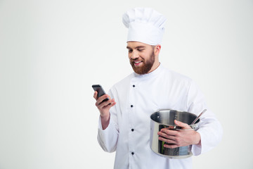 Male chef cook holding pot and using smartphone