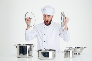 Male chef cook sitting at the table with dishes