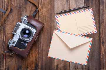 Vintage envelope with post card and retro camera on old wooden table