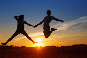 Young happy couple jumping  on sunset