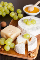 cheeses, honey, grapes and walnuts on a wooden background