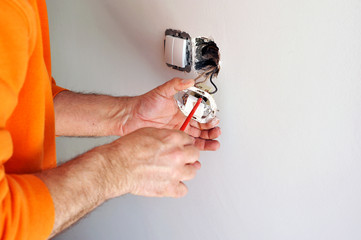 An expert electrician installing new electrical switches
