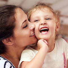 Beautiful smiling young mother hugging her joying happy daughter