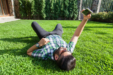 One young fashion middle eastern man with beard and fashion hair style is lying on a grass in a park taking selfie. holding smart phone, tablet, camera and  looking at camera.