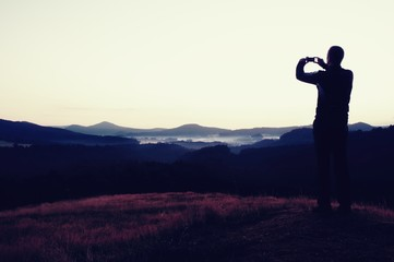 Hiker is taking photo of sunrise by smart phone on meadow. View to hilly landscape.