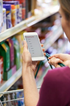 Close Up Of Woman Reading Shopping List From Mobile Phone