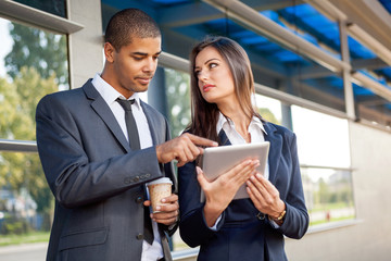 Business man and woman working outdoors with tablet computer in