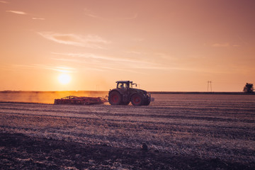 Fotomurales - Tractor on the field by sunset.