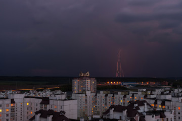 lightning in the night sky over the city houses