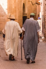 two traditionally clothed moroccans walking in the medina