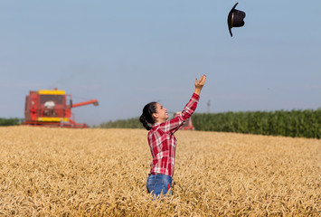 Girl throwing hat in wheat field