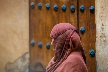 a traditionally clothed moroccan woman walking in the medina