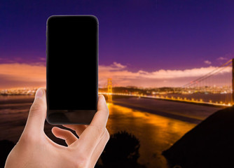 Hand holding mobile with black screen on Golden Gate Bridge background