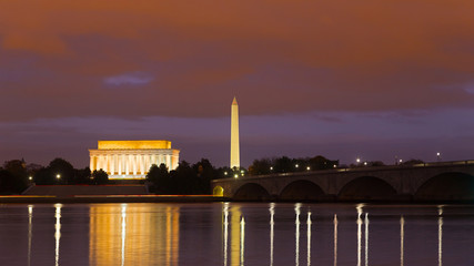 Washington Monument, Lincoln Memorial and Arlington Memorial Bridge at night. Illuminated major national capital attractions with light reflections in the Potomac river.