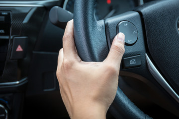 A woman hand pushes the volume control button on a steering wheel.