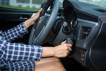 Women driver hand inserting car key and starting engine.