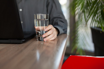 Man Working on a Laptop and Holding a Glass of Water