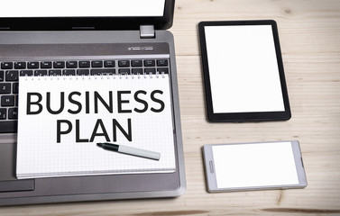 Notebook with Business plan on desk with blank tablet and smart