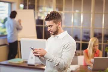 Businessman texting on phone with colleagues working in office