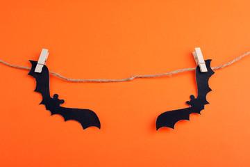 Halloween, bat on a rope on an orange background