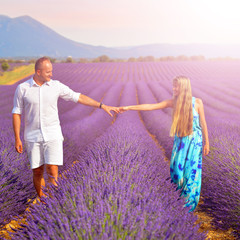 couple holding hands on lavender fields at sunset in Provence, F