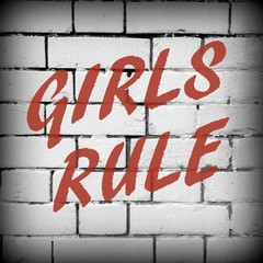 The words Girls Rule in red text on a brick wall background processed in black and white for effect