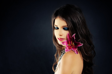 Beautiful Woman with Flowers. Blue Eye Shadow. Wavy Hairstyle