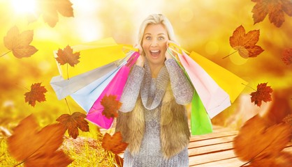 Composite image of blonde in winter clothes holding shopping bag