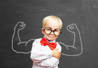 Kind mit Muskeln vor Tafel in Schule