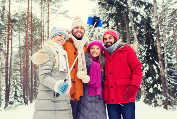 smiling friends with smartphone in winter forest