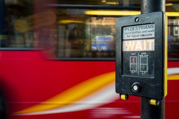A UK pedestrian crossing sign with a blurred red London bus filling the background space.