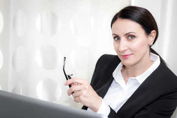 Brunette mature business woman working in a office is giving a over the glasses look in front of the laptop