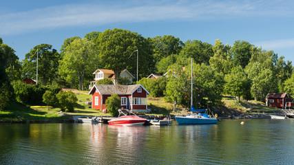 Schwedenhäuser und Boote auf Schäreninsel im Archipelago