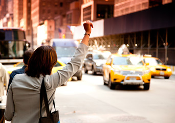 Woman waving for taxi in New York City
