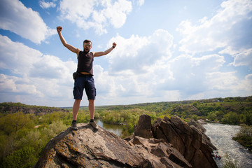 Young man stands on the top of the rock
