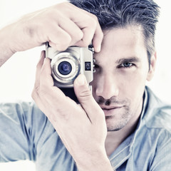 Handsome man taking photo with camera