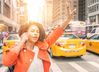 afro american woman calling a taxi in New York near Time square district.